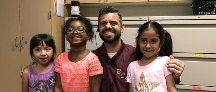 Mr. Kaufmann smiling with three students.