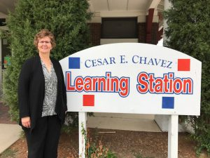 Luanne Rohde standing next to the Cesar Chavez Learning Station sign.