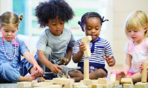 Four children playing with wooden blocks.