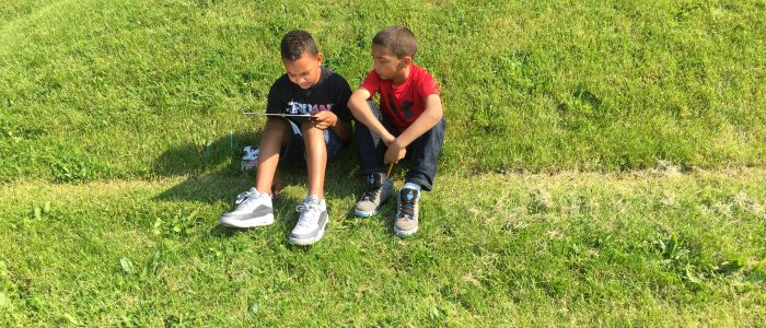 Two boys reading a book on the grass.