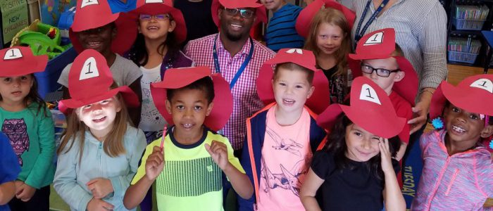 Students and teachers wearing firefighter hats.