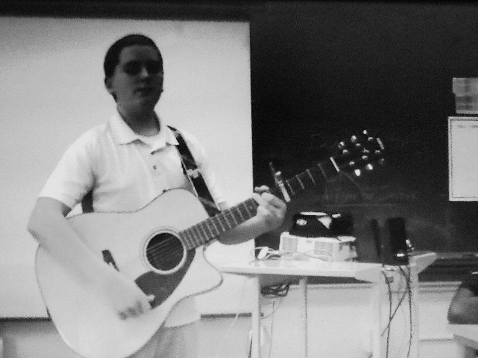 Student playing guitar while performing his Great Depression poem
