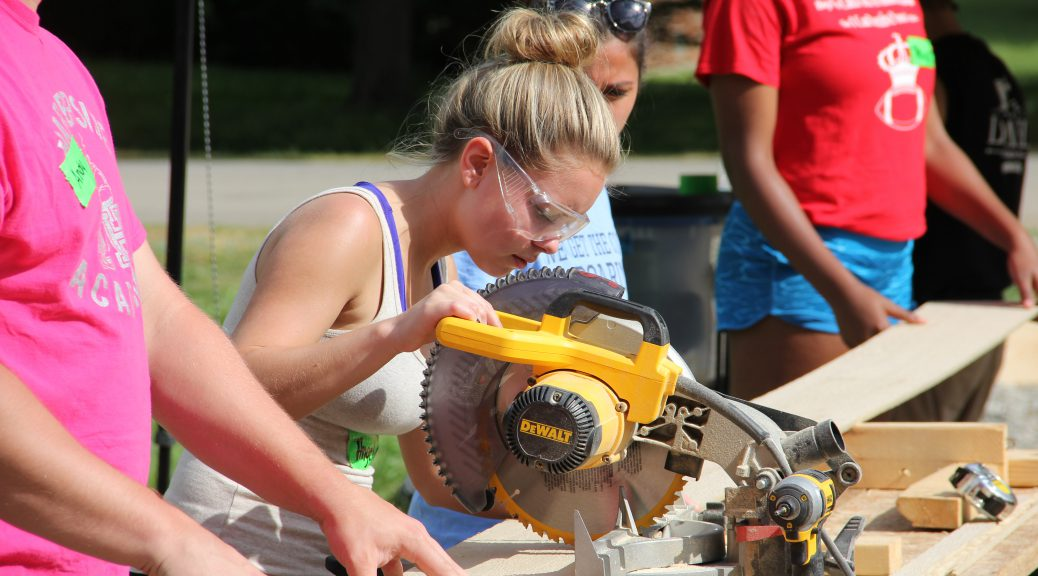 Student operating a stationary saw during her senior project