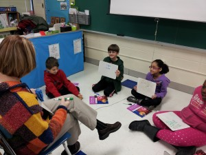 Four students sitting on the floor in front of their teacher.