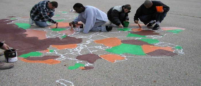 Students painting a U.S. map on the playground concrete.