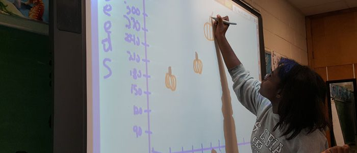 A student drawing on a smart board.