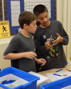 Two male students studying robotics.