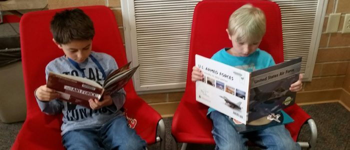 Two boys reading books in red chairs.