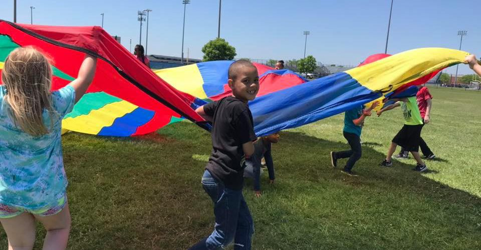A boy smiles as he holds a parachute outside with other students.